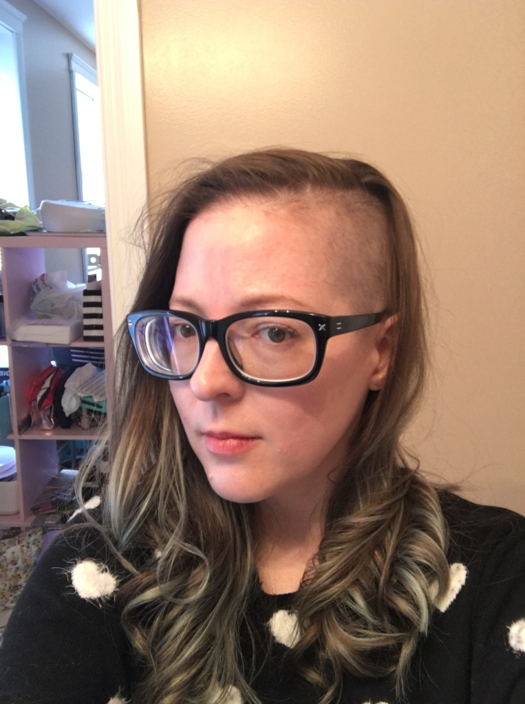 A female presenting person with one side of their head shaved and mint green highlights in the rest of their hair. They're wearing large square glasses and a black sweater with white hearts on it.